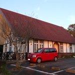 シェ・アン - 夕日に映える建物とお店の赤い車