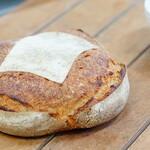 """風土火水 - 料理写真:地元のオーガニック小麦を""""十勝麦の風工房""""の大型の石臼でゆっくり低温で挽くことで風味が良く、栄養価の高い""""全粒粉""""を使用しております。同じ粉から起こす自家製の天然酵母「ルヴァン種」、特許製法でオホーツクの海水をミネラルが豊富なままに仕上げた「宗谷の自然海塩」、「小麦粉・水・塩」だけのシンプルな素材でつくる本物のパンは素材のポテンシャルが決め手となります。"""