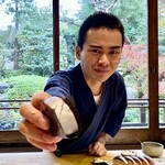 142365461 - サッカー日本代表の長友選手に似たご主人の谷口さん。鯖寿司を手渡しで。