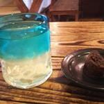 沖縄そば ゆんたく - 沖縄そば定食のドリンク(シークヮーサー)と黒糖のお菓子
