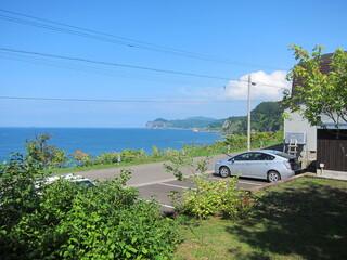エグ・ヴィヴ - 店舗に続く階段途中から見る駐車場と海