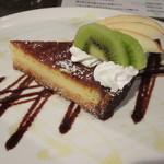 Qoo Qoo Cafe - しっかりした台の上に「ベイクドチーズケーキ」、飾り付けはフルーツとチョコやマンゴ、蜂蜜のソースです。