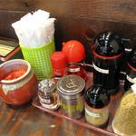 博多ラーメン123 - 卓上には紅しょうが・コショウ・手動スリゴマ・ニンニク・唐辛子ペーストなど。辛子高菜は漬物コーナーで取り放題です。