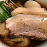 145979106 - 黒い醤油スープにチャーシューやワンタンが乗った中華そばです。
