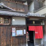 146348527 - 築90年の長屋建築と真っ赤な暖簾がモダンなファサード。