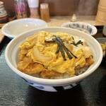 148045207 - カツの載った丼が調理場中央へ運ばれる 少しして親子鍋からとじ卵が丼に盛られる 『お待たせいたしました~かつ丼です』