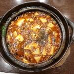 """148886846 - """"四川マーボー豆腐""""のTopView、赤い辣油と大量の挽き肉、白いお豆腐、緑のニラが入り、表面には茶色い山椒がタップリかかっています。"""