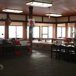 魚見亭 - 広々とした店内の向こう側は270度テラス席で海を臨める