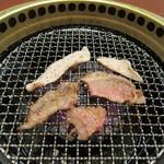 おくう - 牛カルビと豚トロを焼いています