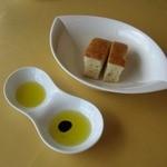 15137254 - パンが届きます。パンの長辺は約5センチ。オリーブオイルとバルサミコ酢入りオイルと。
