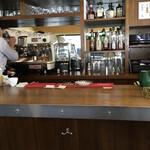 152011243 - LA CIMBALI でカフェを淹れる西谷オーナー、鏡に映る縦ストライプシャツ姿が私。