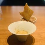 153626764 - ① 玉蜀黍のフラン、ピュアホワイトのスープと燻製フォアグラのパウダー掛け                        パルメジャーノレッジャーノを塗って焼いたチップ