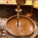 154075996 - 巨大なお鍋にグルグル回るチョコレート色のカレー!