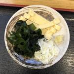 元祖武蔵野うどん めんこや - ネギ、ワカメ、油揚げ、おろし生姜が付いてきます。