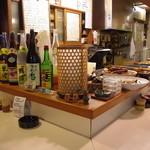 お食事処こやま - カウンターに並んだおばんざいの大皿と、焼酎と梅酒各種