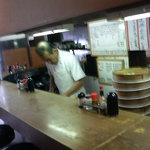 グリルニュートモヒロ - ステップを踏みながら料理をするおじさん