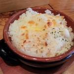 15846874 - りぞ飯(小)150円 ご飯の上にチーズを乗せてオーブンで焼いたものに粉チーズをかけています。