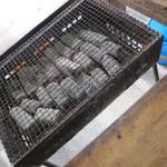 牡蠣小屋 住吉丸 - 炭火焼です。灰が舞います