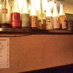秋葉原漁港 快海 - 果実焼酎の向こうに厨房