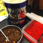 拉麺帝国 - 卓上。紅しょうがやコショウに加えて、フレーク状のガーリックがあります。