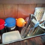 博多一双 - 辛子高菜、紅ショウガ、粒ニンニク(クラッシャー付)、擂りゴマ、コショウが置いてある