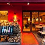 ピッツェリア ピッキ - 積み重なる薪と真っ赤な店頭がピッキです。
