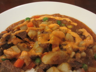 アルコイリス 川崎店 - 牛肉ポテト煮込トマトソースに辛口のソースをかけて