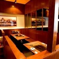 ゆかり - 簡単な仕切りがあるテーブル席で鉄板を囲んで自慢の大阪の味を