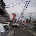 麺屋 侍 - 街路樹付近の白い車の正面が当店。