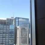 テンクウ - 窓側手前からは立ち並ぶビル群が…ビルに映る雲が美しい