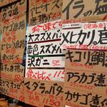 だぼ - カウンター前の壁全体にびっちり貼ってあるダンボール紙の札に書かれたメニュー。 初めて聞く魚の名前も色々見かけます。
