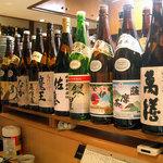 秋葉原旨い魚と焼酎.地酒 美味研鑽 TETSU - 店内には沢山の焼酎や日本酒の瓶が