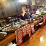 炭火焼との山 - カウンター上には大皿料理が並ぶ。