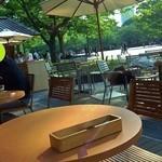 パークサイドカフェ - ウッドデッキのテラス席からの眺め。緑に囲まれ、そよぐ風が心地よい