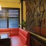 欧風カレー ボンディ - 焦げ茶の柱や梁に茶のテーブルに赤のソファが何ともレトロな空間