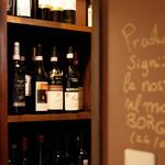 イル カンティニエーレ - 店内のワインセラー。約350種のイタリアワインと壁には来店された生産者からのメッセージが。