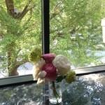 カフェドゥラプレス - 机の上の花と外の新緑