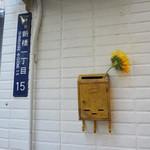 ピッツェリア テルツォ オケイ - お店の外壁にヒマワリ一輪