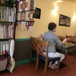 スリランカ料理 ラサハラ - 女性1人でも気兼ねなく来店、手前の本棚必見、入り口右手に4人掛けテーブル2卓あり