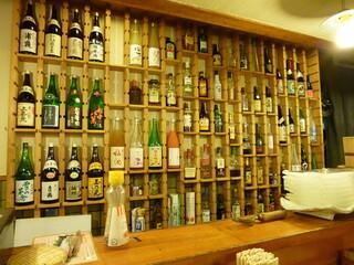 刺身BAR 河岸頭 - バックバーには日本酒やウイスキー、焼酎の瓶がならぶ。