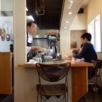 コアンドルー - テーブル石より、カウンターおよび厨房を見る
