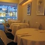20914838 - 白を基調としたテーブル席。夜は、ちょっと暗い