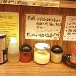 横浜家系らーめん 二代目武道家 - 卓上調味料はこんな感じ。おろしニンニク、おろし生姜、豆板醤にお酢、すりごま器、胡椒など。平均的な家系ラーメン店ですな。
