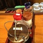 太陽 - 卓上の調味料。手前から、手作りラー油、ガーリック粉、胡椒、高麗人参入り酢。