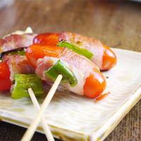 鳥一番 - ウィンナー肉巻マヨネーズ☆一串150円☆昔懐かし赤ウィンナーを豚肉で巻いて、ししとうをはさんで焼きあげます。見た目も可愛く、シンプルに旨い!【影で一番人気】のある一品です!!