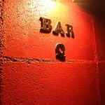 Bar Q - 真紅のブロックで静かに主張する店名のプレート