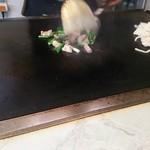 21794266 - 鉄板の端っこにうどんを出しておいて、ホルモン、野菜(ネギ、玉ねぎ)を炒めて、合体させていきます。