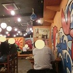 浜焼太郎 - 大漁旗の飾られた店内。向こう側に、テーブル席と小上りがあります。ここはカウンター席と二人掛けテーブル席。