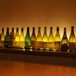 フルールパルフ - カウンターの奧にはバックライトとワインの空き瓶が幻想的に。