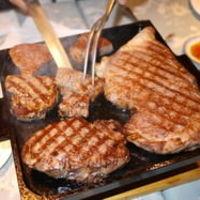 3匹の子ぶた - 櫓(やぐら)ステーキプランは、お肉をお客様の目の前でカットします。大きな1ブロックのお肉は迫力満点。炭火でベリーレアに焼いたお肉を鉄板に乗せてテーブルまでお持ちします。